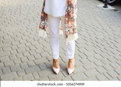 Stylish woman in white jeans and light pink leather pumps walking on the city street. Summer outfit, fashion trends, street style look