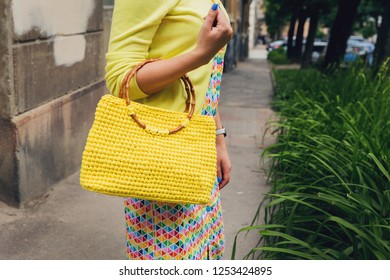 Stylish woman with yellow knitted handbag walking on the city street. Handmade knitted bag