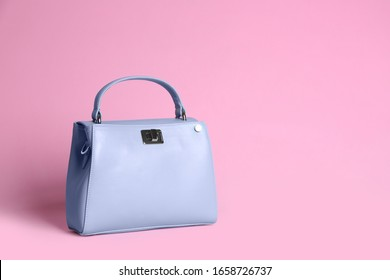 Stylish woman's bag on light pink background. Space for text