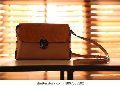 Stylish woman's bag on shelf in boutique
