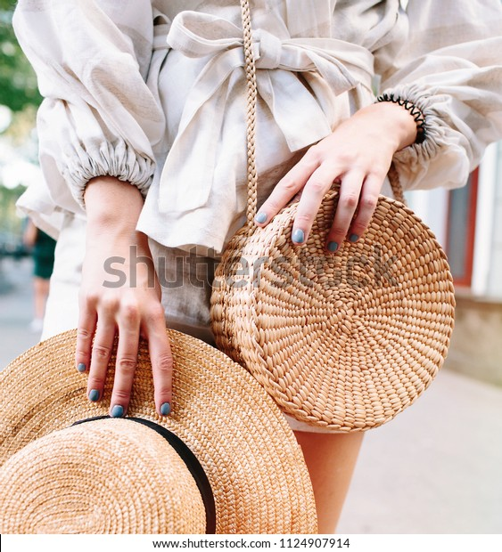 Stylish woman's outfit. Nature stylish top. Straw bag. White dress.Woman hands with fashionable stylish nude rattan bag and straw bag outside. Stylish young woman fashion details
