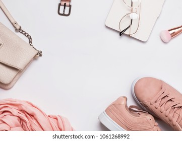 Stylish woman's outfit for spring or summer. Flat lay with pink sneakers, scarf and other accessories.