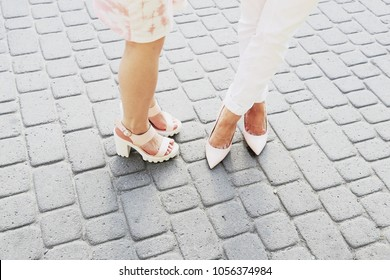 Stylish women in white jeans and light pink leather pumps walking on the city street. Summer outfit, fashion trends, street style look