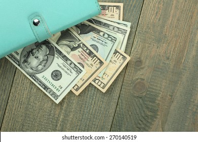 Stylish women's purse with money on wood background