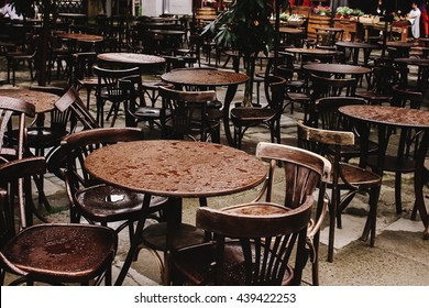 stylish wooden chairs and tables empty at rainy day on streets of europe city