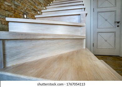 Stylish wooden contemporary staircase inside loft house interior. Modern hallway with decorative limestone brick walls and white oak stairs.