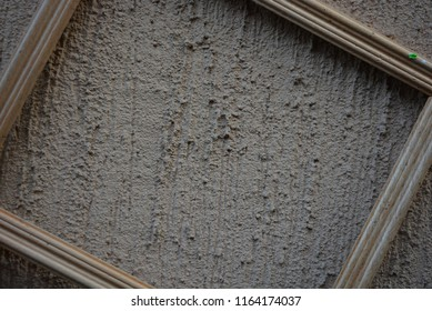 Stylish wooden frame for photos of white wood on the background of an external building wall with a brown caro branch and grains