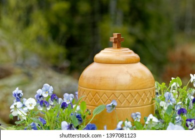 stylish wooden funerary urn standing in nature among blue and white violets ready for spreading of the ashes