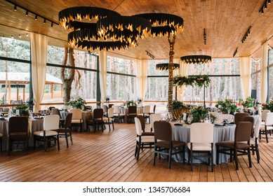 Stylish wooden restaurant decorated by greenery with black loft lamps.  Wedding reception. Banquet. Decor
