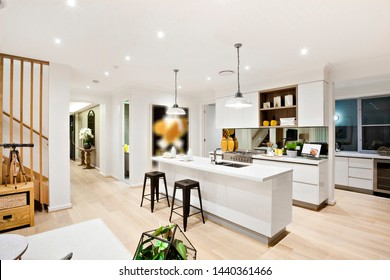 A stylish wooden staircase in front of a stylish modular kitchen with white counters and cabin and a snack counter with two stools
