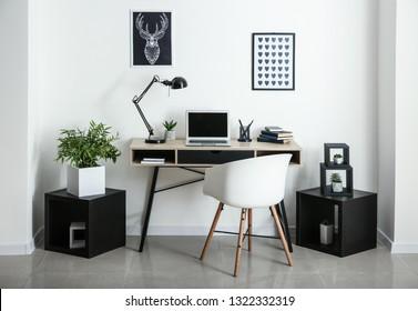 Stylischer Arbeitsplatz mit Laptop im Zimmer