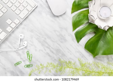 Stylish workspace combining nature and technology. Flat lay composition on marble background, with copy space in the middle.