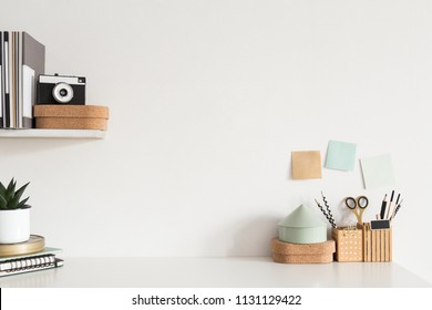 Stylish workspace desk with accessories, houseplant, sticky notes, camera on white wall background.