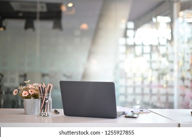 Stylish workspace with laptop computer, office supplies, flower at office. desk work concept.
