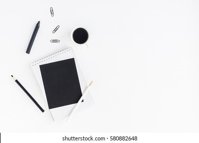 Stylish workspace with notebook, cup of coffee, paper blank, pencils. Business concept.  Flat lay, top view.