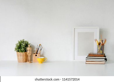 Stylish workspace with poster, book and gadget. Workplace desk and copy space.
