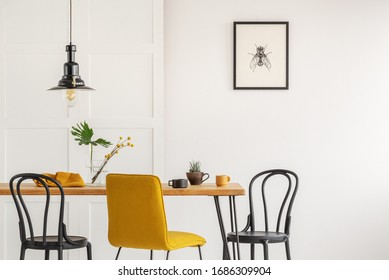 Stylish yellow chair at wooden dining table in trendy interior - Shutterstock ID 1686309904