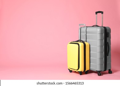 Stylish yellow and grey suitcases on pink background. Space for text