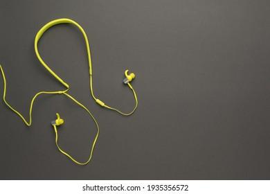 Stylish yellow headphones on a dark gray background. Equipment for listening to music.
