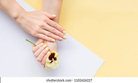 Stylish yellow trendy female manicure. Beautiful young woman's hands on yellow and white background.
