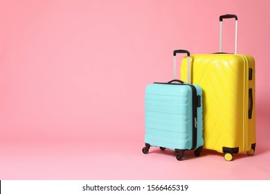 Stylish yellow and turquoise suitcases on pink background. Space for text
