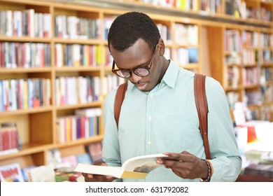 Stylish young African American male in shirt and eyewear looking through book in bookstore standing against shelves background. Black male tourist exploring local bookshops while traveling abroad