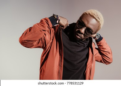 Stylish young african american man straightens his jacket isolated on light background