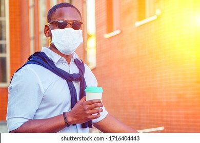stylish and young African student American man in medical mask holding coffee paper mug in summer in park red brick building background