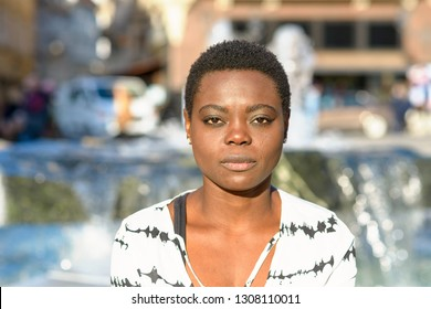 Stylish young African woman with a calm deadpan expression staring quietly at the camera standing in front of a city fountain