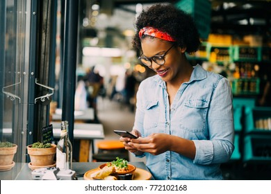 Stylish young African woman smiling while sitting alone at a counter in a bistro taking photos of her food with her smartphone