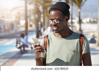 Stylish young Afro American male looking at screen of his smart phone with happy smile, about to answer his girlfriend's call while on vacations abroad. People, lifestye and modern communication
