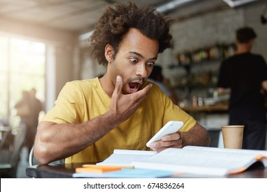 Stylish young Afro American male student with earring dressed in yellow T-shirt having surprised expression after recieving message from his groupmate finding out that he will have exam in an hour.