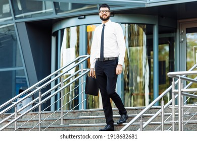 Stylish young bearded businessman in business clothes near office building in the city