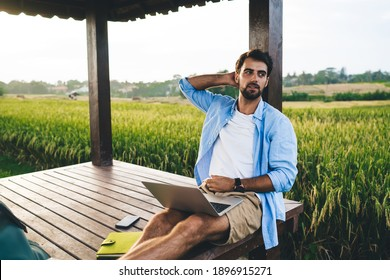Stylish young bearded businessman in casual clothes working on project on netbook sitting in wooden pavilion during summer holidays in countryside