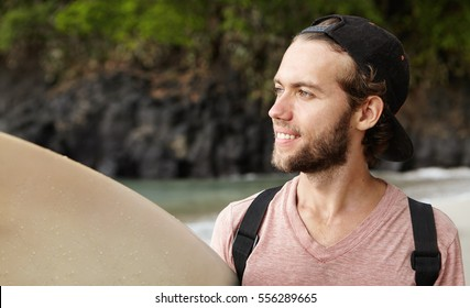 229f97eb620 Stylish young beginner surfer wearing baseball cap backwards looking at  ocean with happy and inspired smile