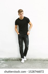 Stylish young blond man in black t-shirt and black jeans stands on white background.