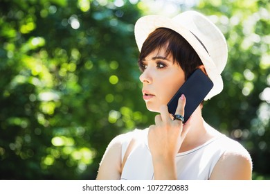 Stylish young brunette woman in hat talking on the smartphone in the park. Self-confident business woman talking on the phone on the street. Smart woman in white hat