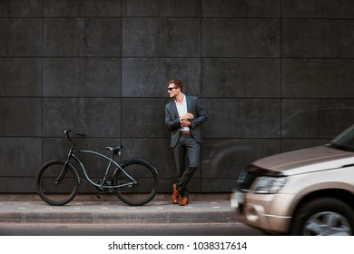 Stylish young businessman in sunglasses stands near a bicycle with his back against a brickgray wall