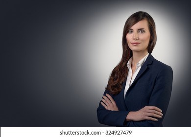 Stylish young businesswoman with a friendly expression looking directly at the camera, closeup of her face on a grey background with copy space
