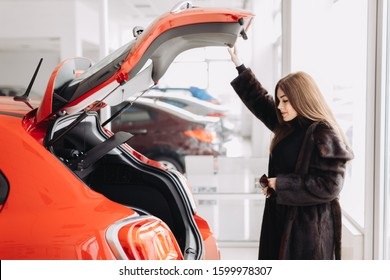 A stylish young businesswoman wearing a brown fur coat,sunglasses, a red skirt and  a black turtle neck sweater is checking a new car. There is Fiat sign on the wall in a car store.