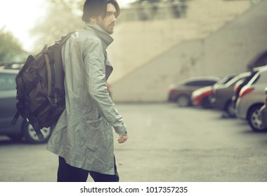 Stylish young caucasian man in silver grey coat and backpack passing by parking lot. Sun flare. Blurred. Vintage effect. Clothes advertising campaign concept.