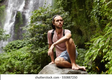 Stylish young Caucasian tourist with backpack relaxing barefooted on big stone with gorgeous waterfall behind him. Bearded backpacker sitting on rock during trip in mountains and looking tired