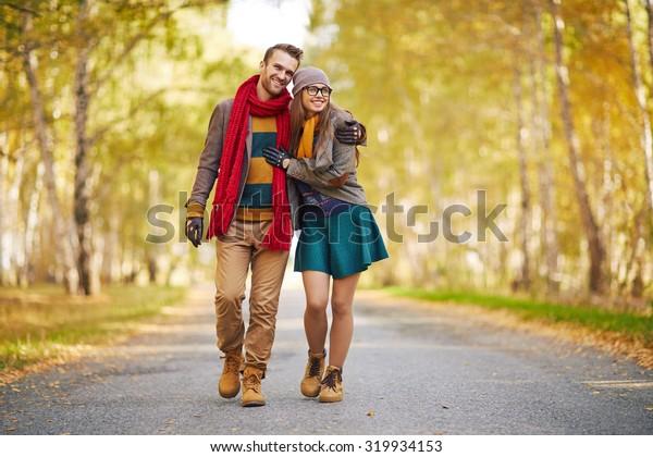 Stylish young couple enjoying walk in park