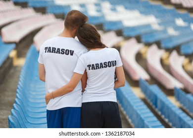 Stylish young couple hugging at a sports stadium outdoor. Smiling couple sitting together on empty sports tribune. fans sitting on empty stadium sector on competition.love story concept