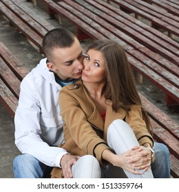 Stylish young couple hugging at a sports stadium outdoor. Smiling couple sitting together on empty sports tribune. love story concept.