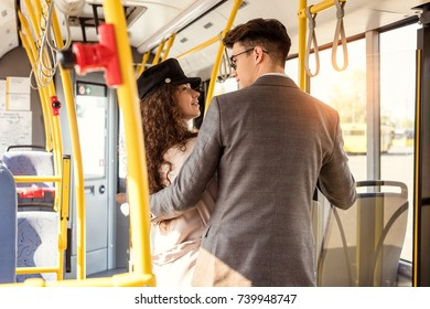 stylish young couple looking at each other while riding in public transport