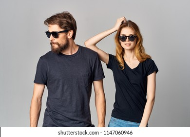 Stylish young couple wearing glasses in black T-shirts.