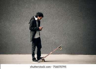 Stylish young dreadlocks hipster skater with headphones looking at smart phone standing on long board.