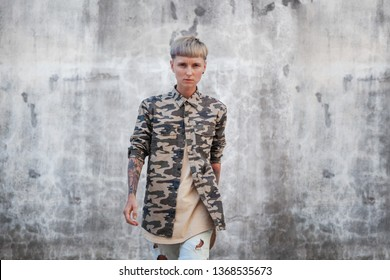 Stylish young European woman brutal with short haircut, rebel, a variety of people, serious and powerful, urban style