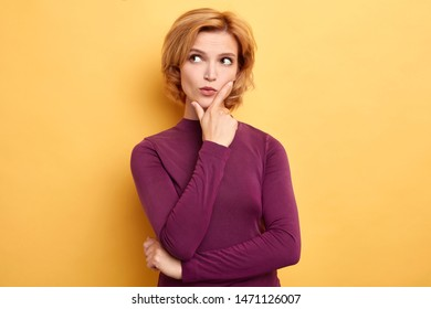 stylish young fair-haired woman touching her chin and looking sideways with doubtful and sceptical expression. close up portrait. isolated yellow background. copy space
